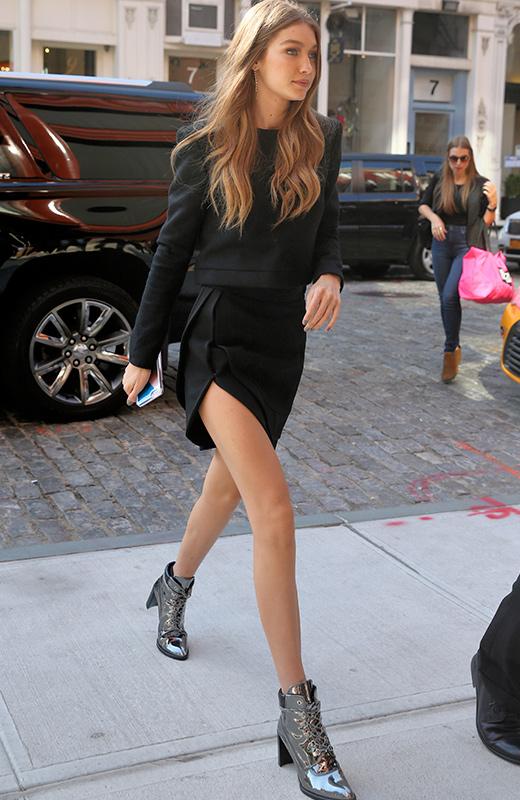Gigi Hadid con minifalda negra y botines plateados