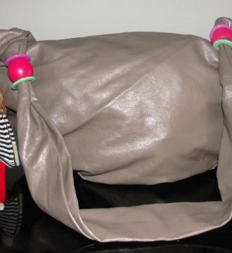 Bolso gris con muñeca colgante