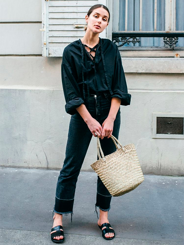 Total black look con bolso de paja
