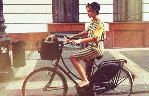 Mujer en bicicleta con perro en la cesta
