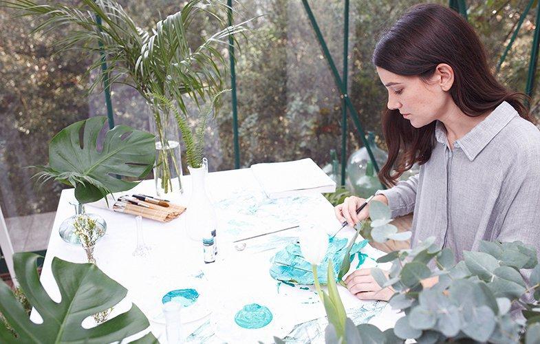 Lara, pintando sobre una hoja de Costilla de Adán.