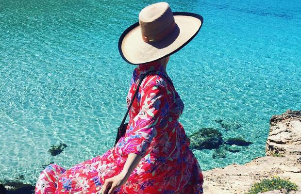Mujer con sombrero en la orilla del mar