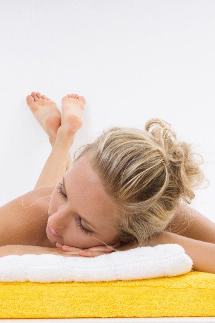 Mujer durmiendo sobre toallas