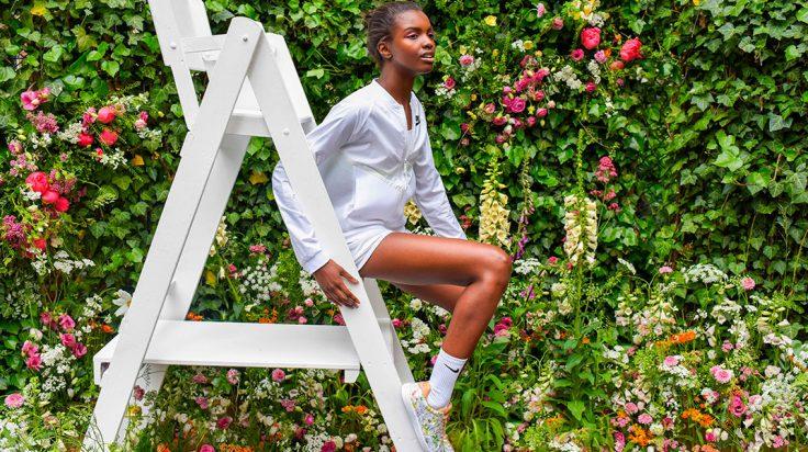 Modelo de color sentada en una silla posando con las zapatillas Nike